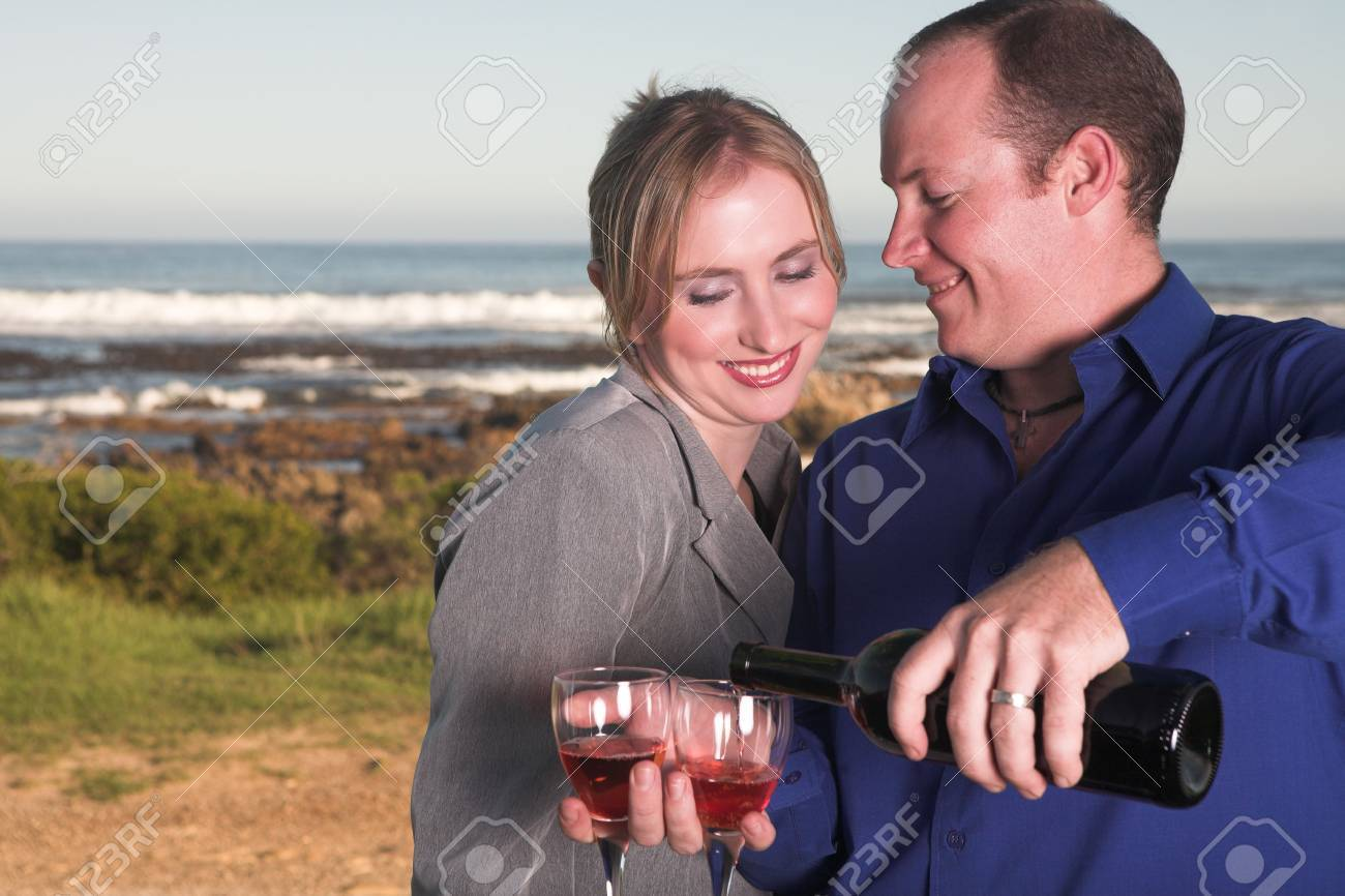 Young adult Caucasian couple drinking wine outdoor next to the ocean Stock Photo - 3341791