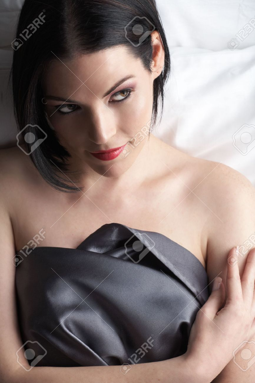 Sensual naked young Black haired adult Caucasian woman, wrapped in a charcoal colored satin, silk sheet on a bed in her bedroom. High contrast lighting. Stock Photo - 3921914