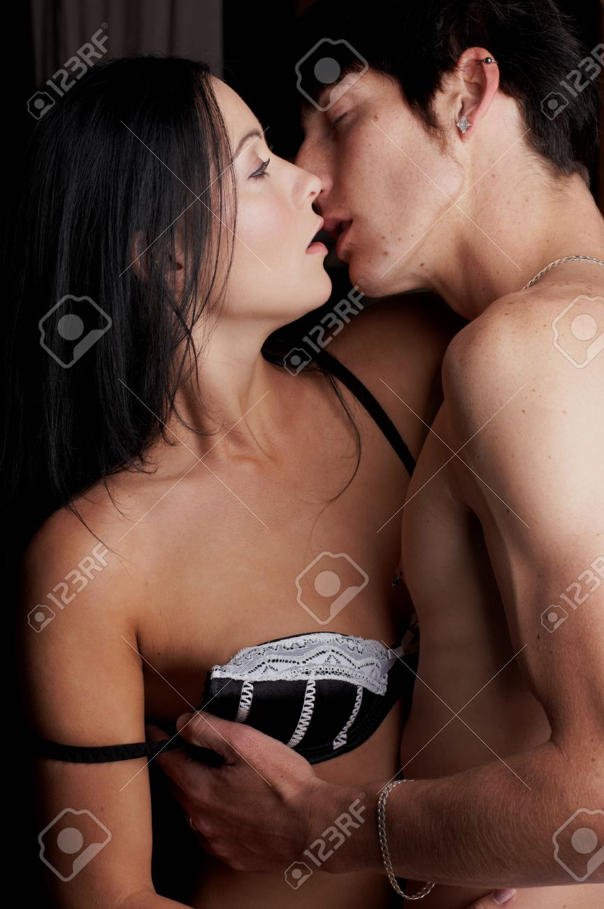 Stock Photo Young Adult Caucasian Couple In Passionate Embrace And Undressing Each Other During Sexual Foreplay
