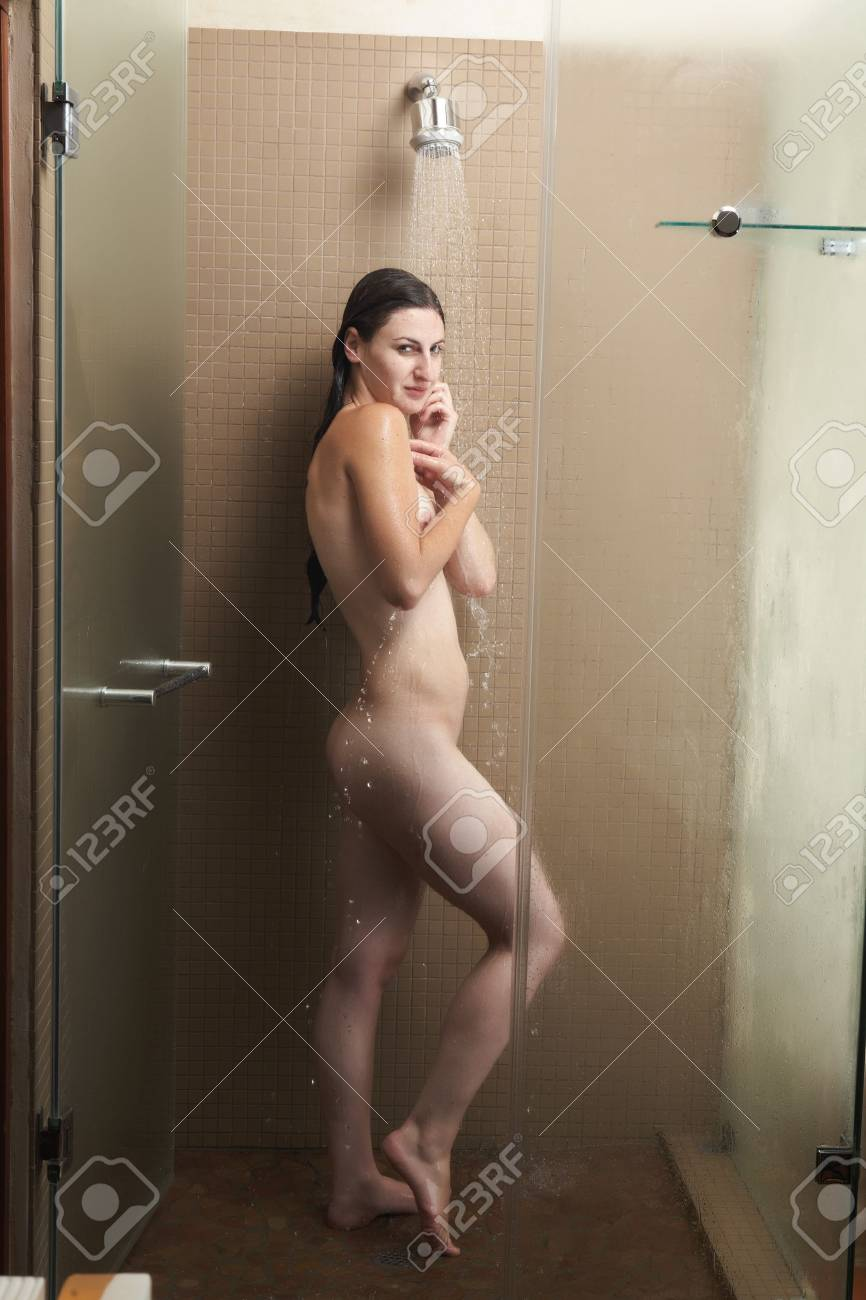 Sexy young adult Caucasian woman with long auburn hair and petite breasts taking a shower in a tile and glass modern bathroom. Stock Photo - 8179988