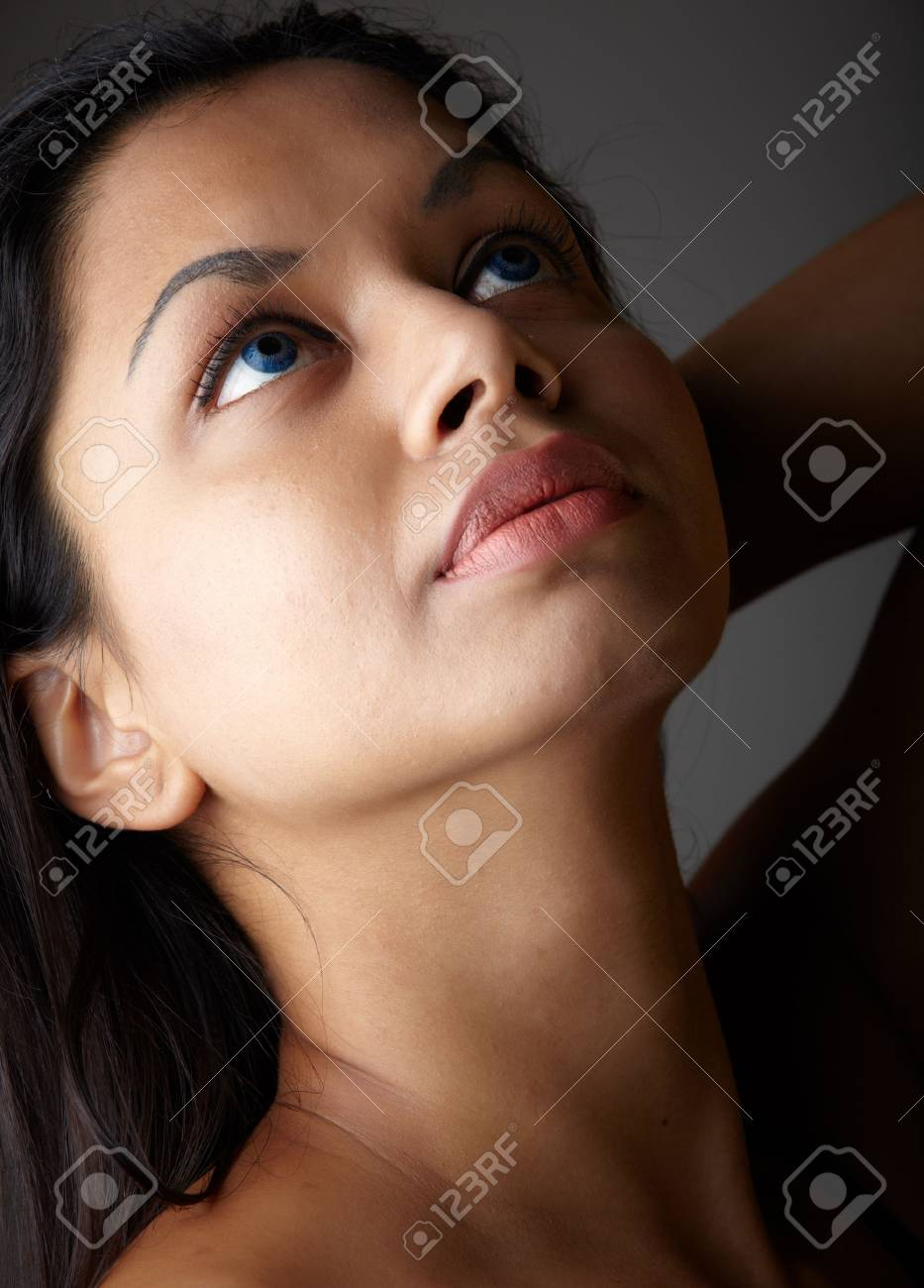 Young voluptuous Indian adult woman with long black hair wearing black lingerie and blue coloured contact lenses on a neutral grey background. Mixed ethnicity Stock Photo - 9048858