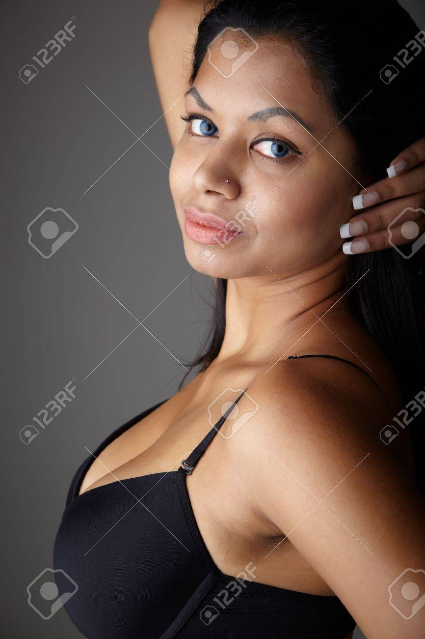 Young voluptuous Indian adult woman with long black hair wearing black lingerie and blue coloured contact lenses on a neutral grey background. Mixed ethnicity Stock Photo - 9048893