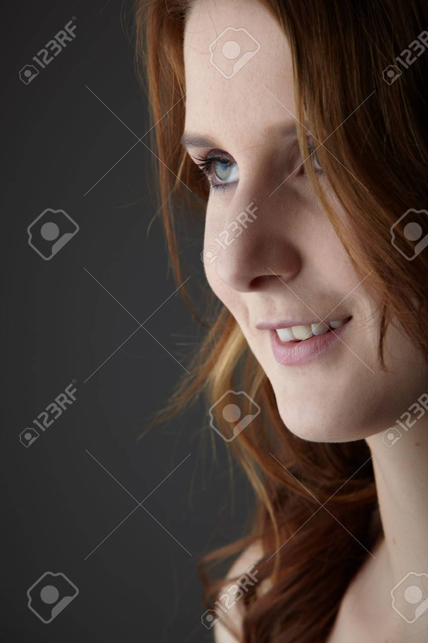 Portrait of a young caucasian adult redhead woman with green eyes and very fair skin on a neutral grey background Stock Photo - 12804888