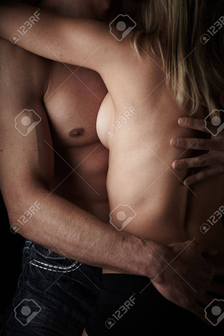 Young and fit caucasian adult couple in an embrace. Semi-nude and topless against a dark background . Stock Photo - 13644603