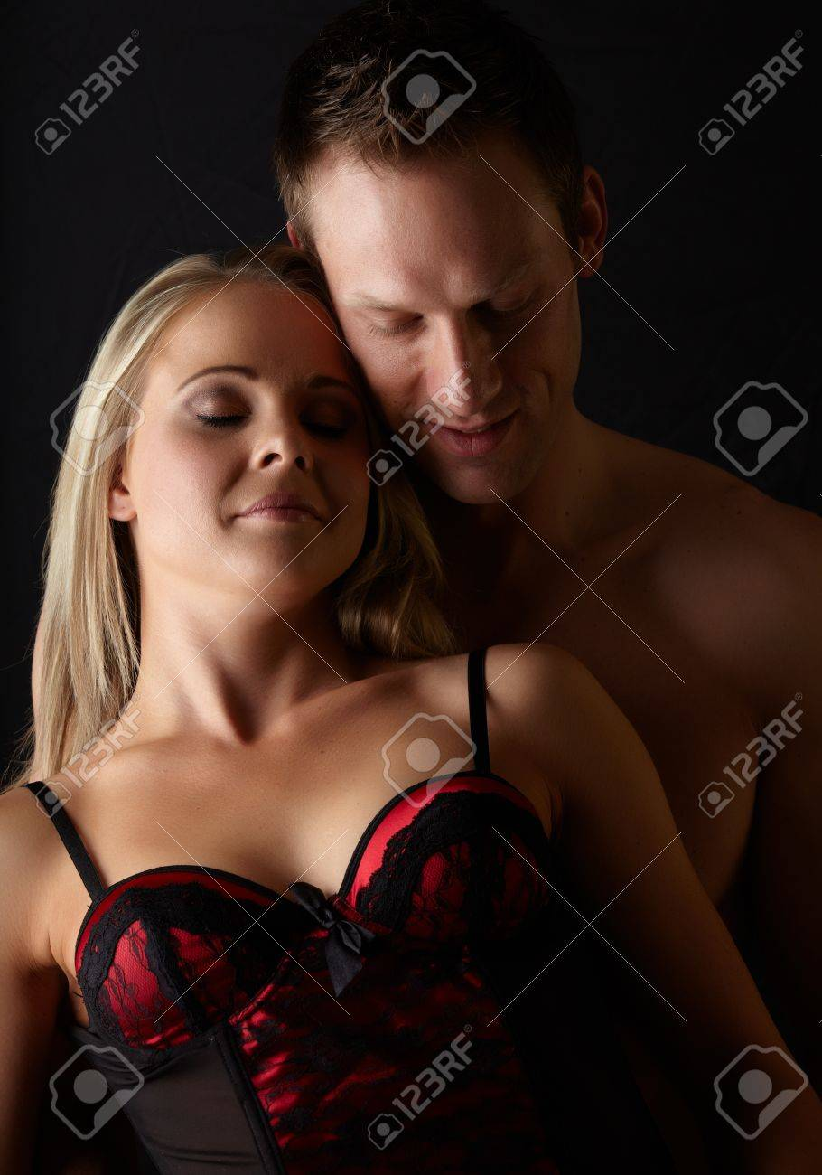 Young and fit caucasian adult couple in an embrace  Semi-nude and topless against a dark background with the woman wearing a sexy red and black lace corset Stock Photo - 13872199