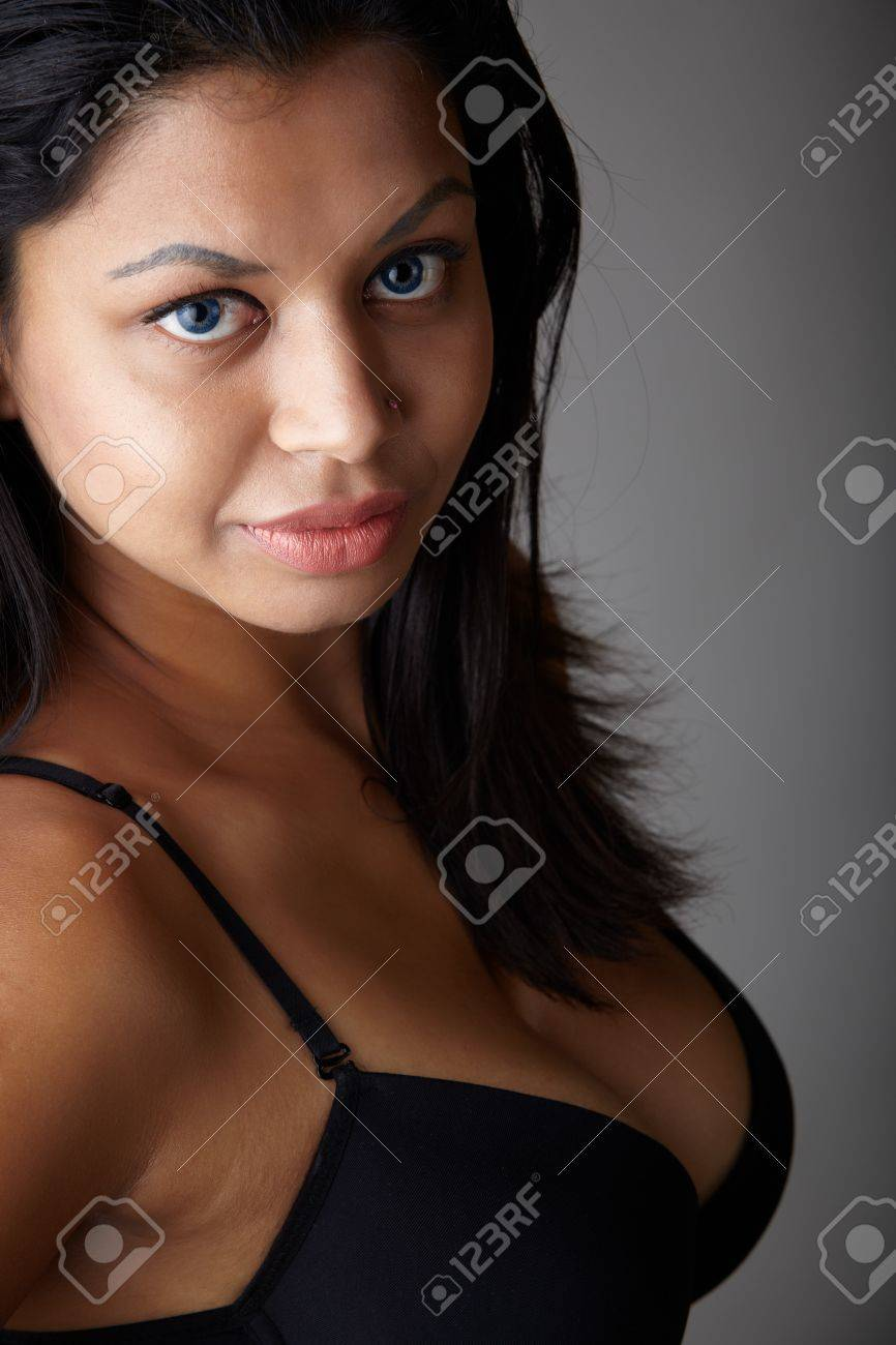 Young voluptuous Indian adult woman with long black hair wearing black lingerie on a neutral grey background Stock Photo - 13872213