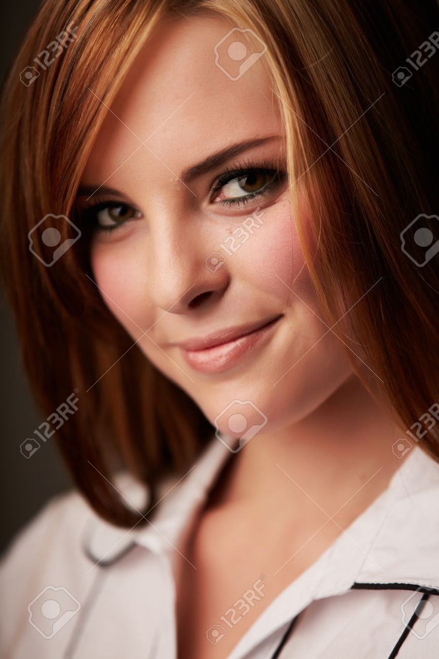 Beautiful young caucasian adult woman with long auburn red hair on a plain background, wearing a white button shirt Stock Photo - 14227636