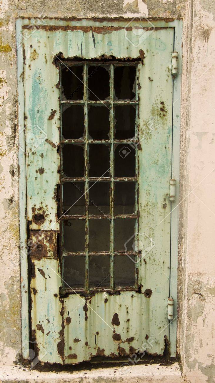 A rusty door at the old Alcatraz maximum security prison in San Francisco. This door, once painted green, has rusted out over the years due to a lack of maintenance and is now a symbol of neglect. Stock Photo - 2374295