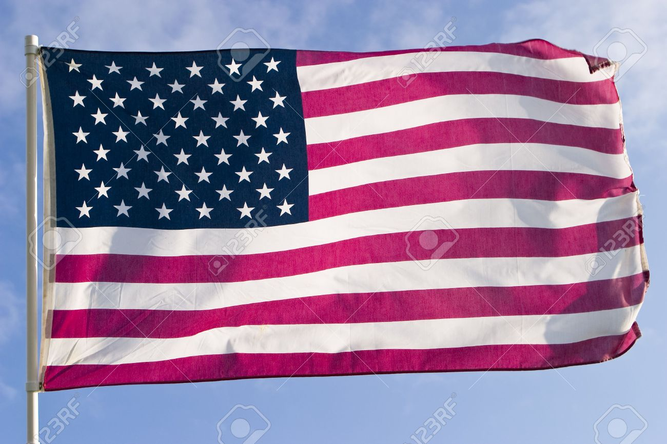 The American flag, flying in a strong wind, is almost perfectly horizontal. Every stripe and every star is visible. Stock Photo - 2430137