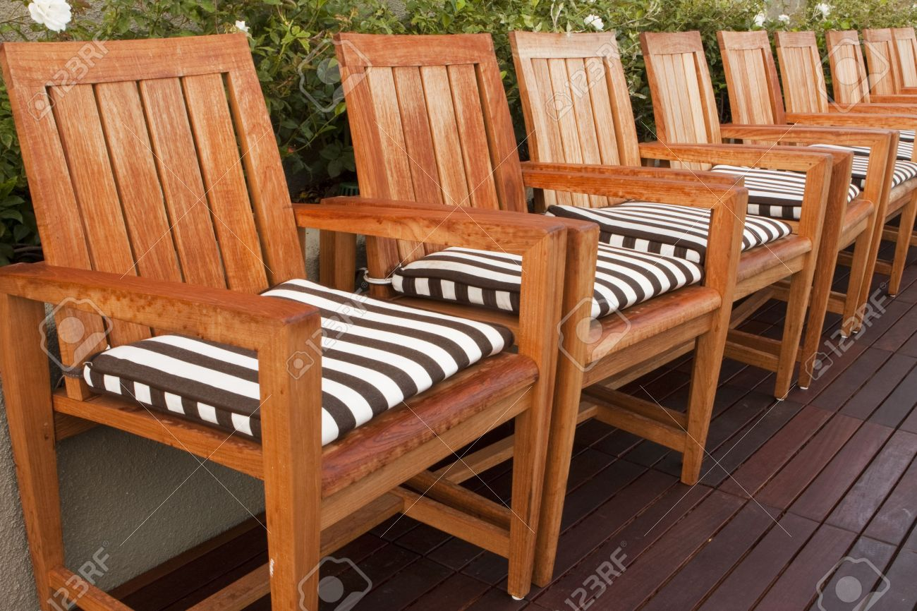 A Line Of Teak Wood Chairs With Black And White Striped Cushions Arranged  In A Row