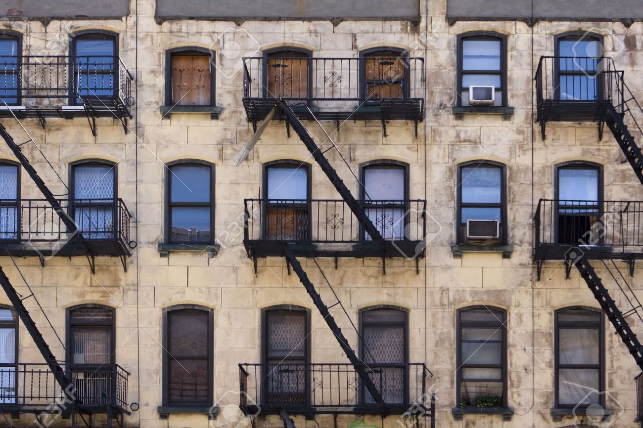 Three Floors Of Windows With Fire Escapes On The Facade Of A