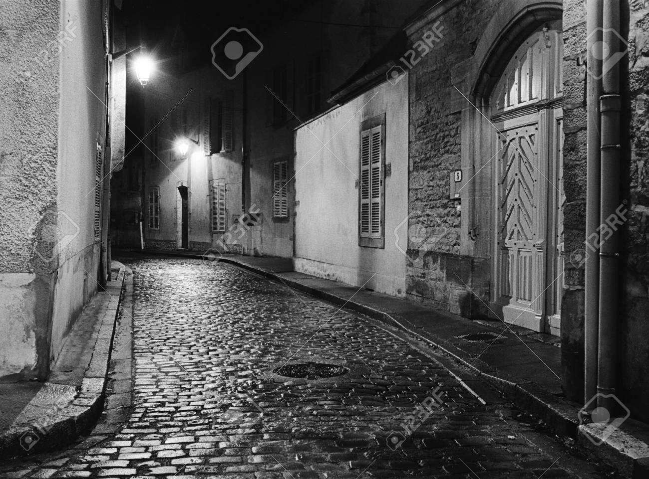 Black and white film a night scene captures an empty alleyway in beaune france where the wet cobblestones are