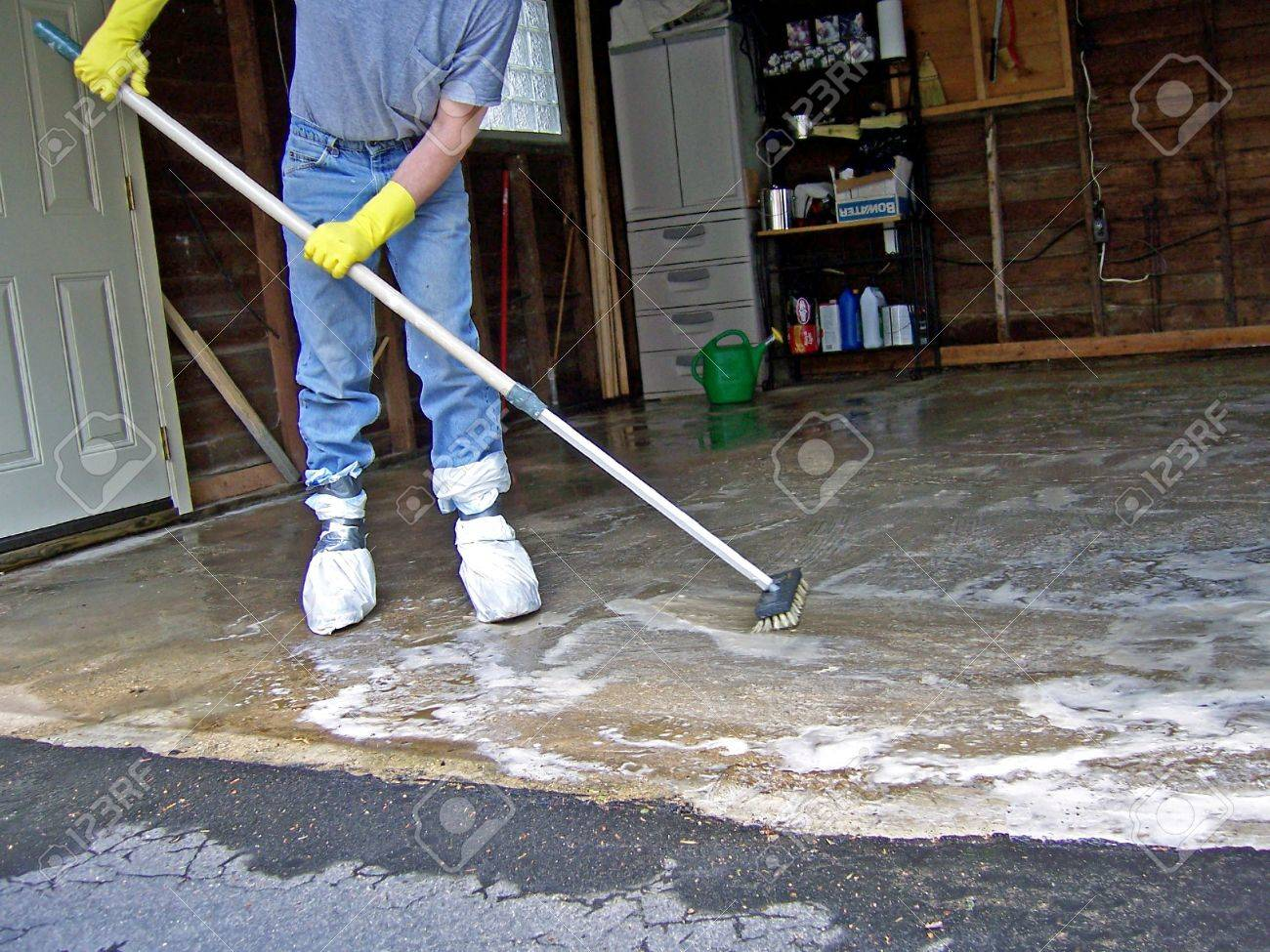A Man Cleaning Garage Floor With Soap Stock Photo   921836