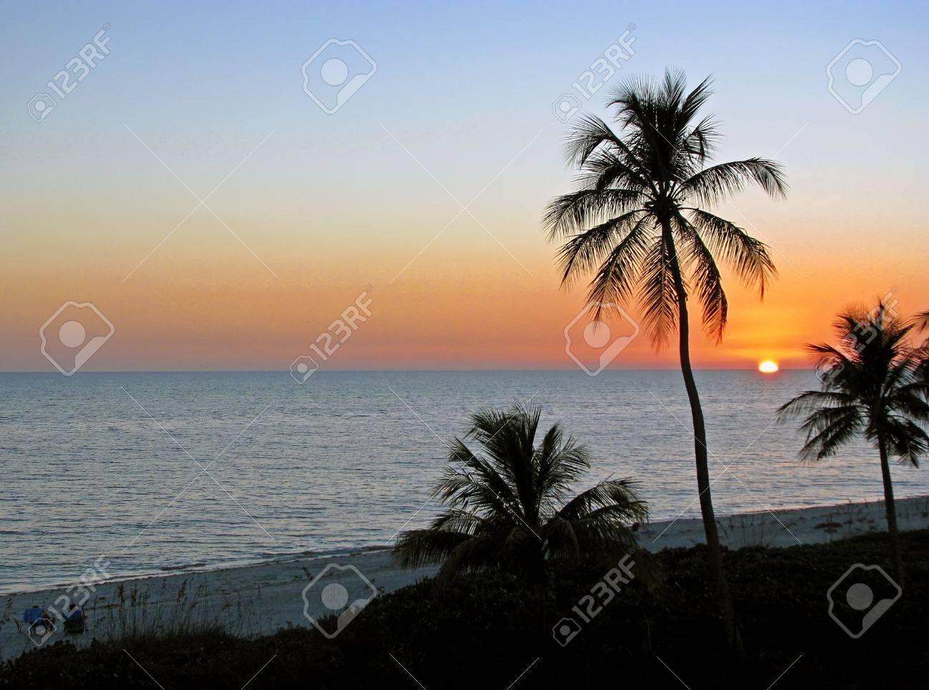 Couple Sitting In Beach Chairs Watching Sunset Stock Photo