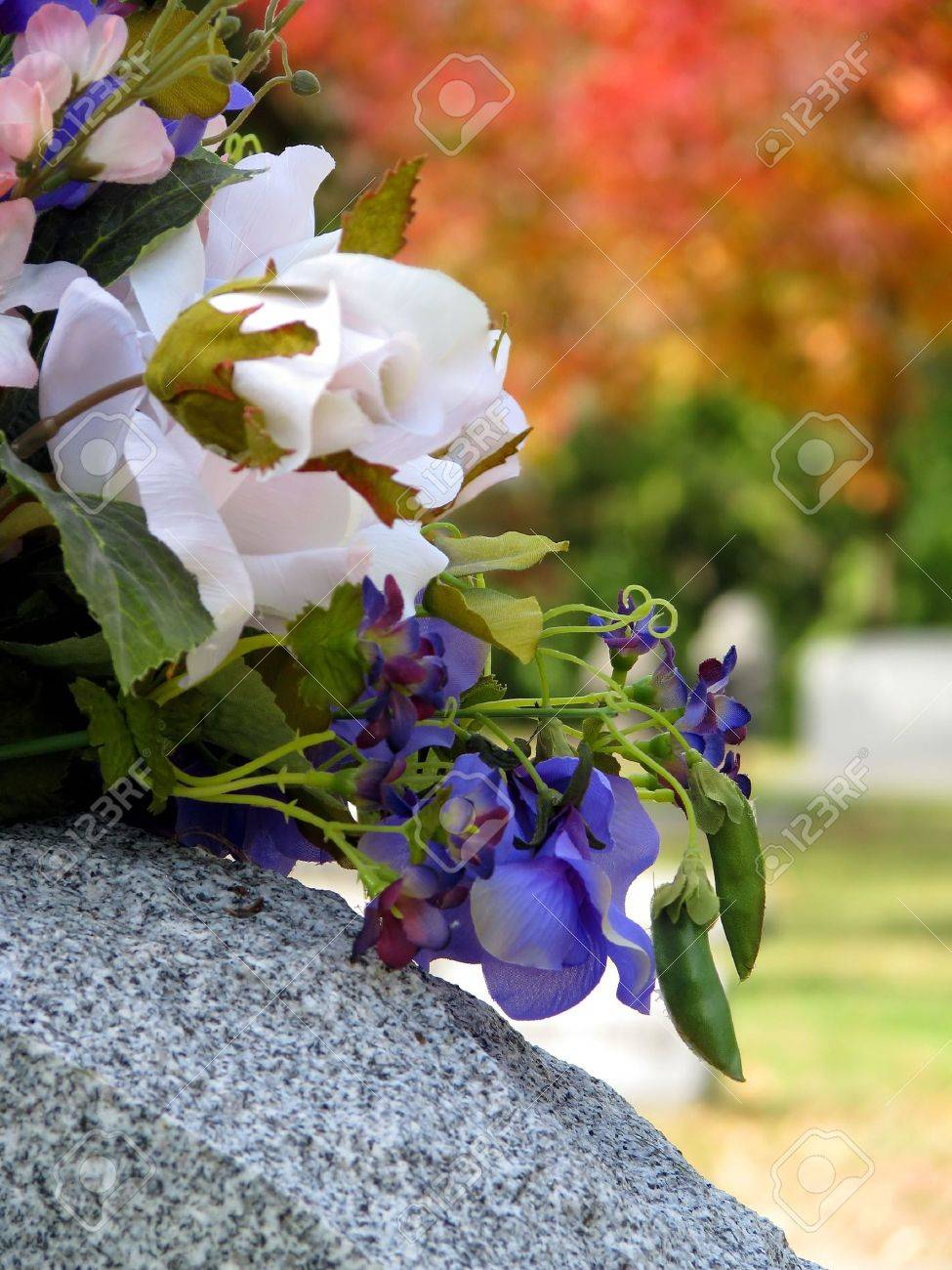 Silk flowers on a cemetery grave headstone stock photo picture and silk flowers on a cemetery grave headstone stock photo 3709290 mightylinksfo