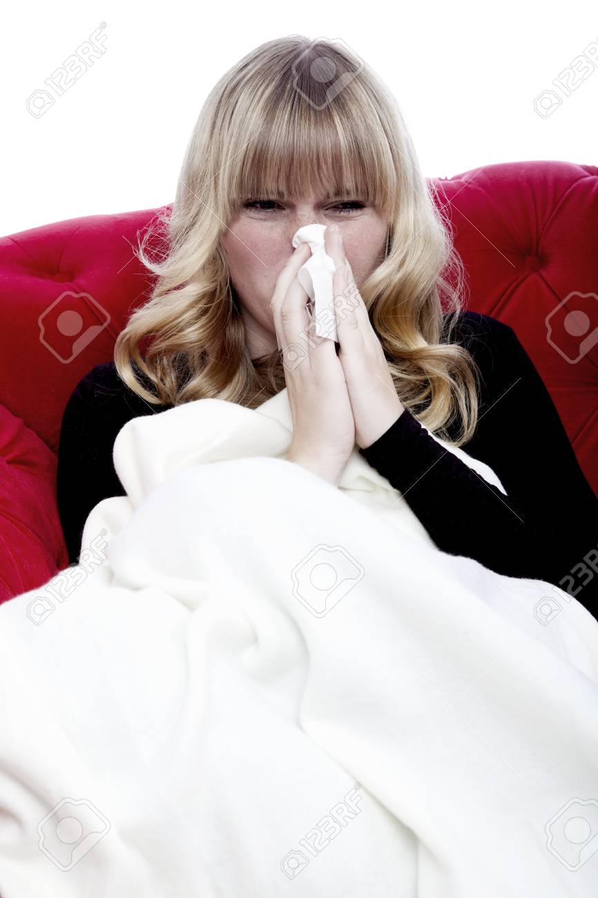 young beautiful blond haired girl with hanky and illness on red sofa in front of white background Stock Photo - 15834882