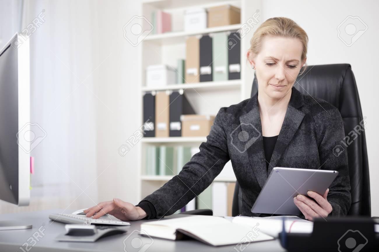 Sérieux affaires en costume noir assise à son bureau et tenant une