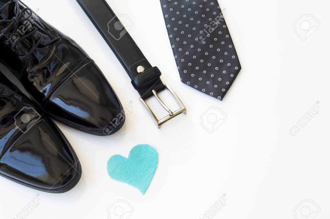 Father's Day Concept. Black Patent Leather Shoes, Tie, Belt, Eyeglasses and heart on a white background. Copy space for text - 149178272