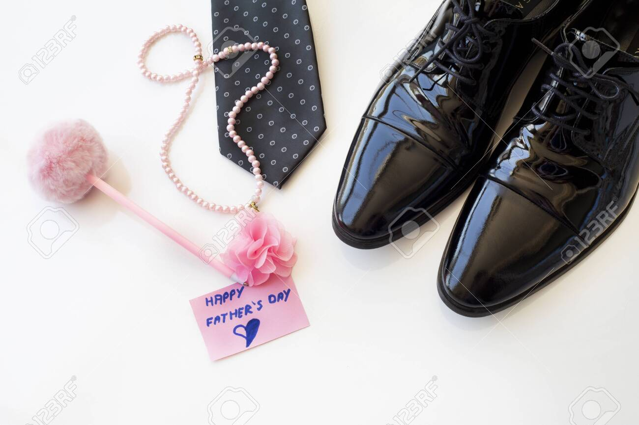 Father's Day Concept. Black Patent Leather Shoes, Tie and pearl necklace with greeting card on a white background. Copy space for text. Father's daughter. - 149178474