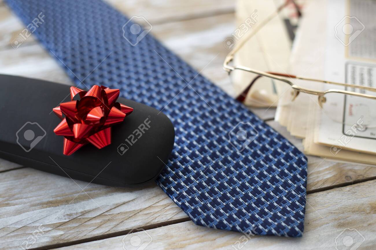 Father's Day Concept. Gift Box with Tie, Reading Glasses and Newspapers on wooden background. Copy space for text. - 151220143