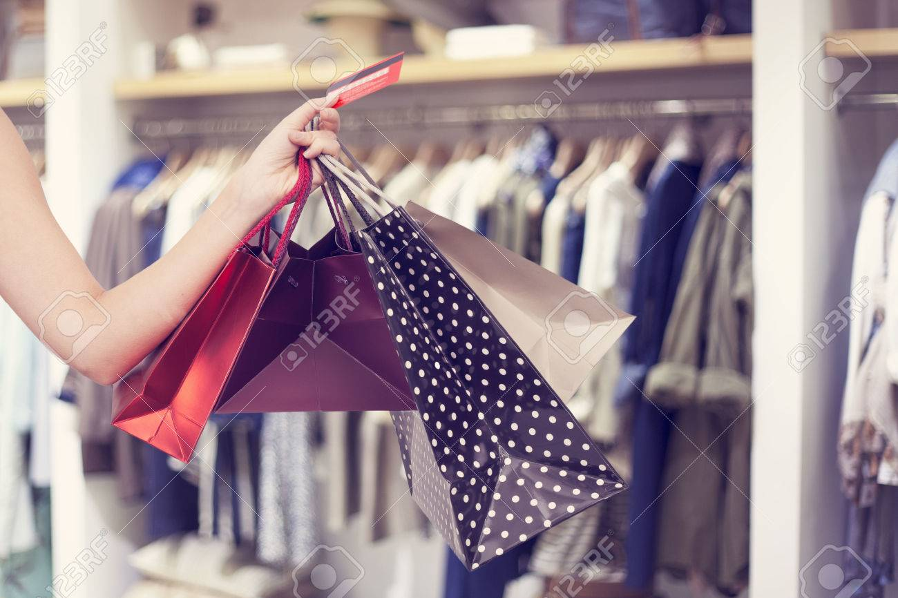 Woman holding shopping bags and credit card - 53560557