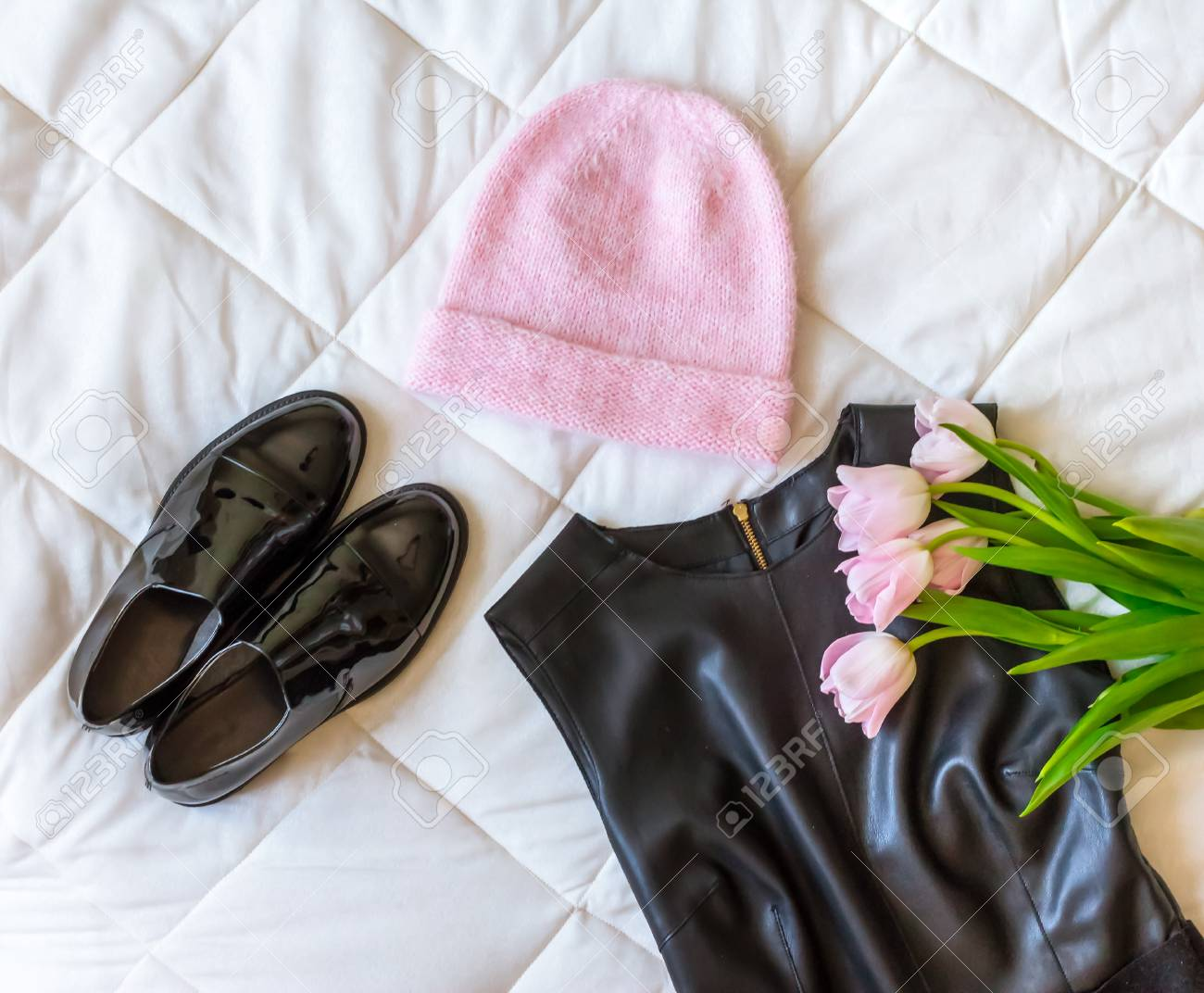 bf5d9a2e540a95 Pink hat, black leather dress, black lacquered shoes and a fresh pink  tulips Stock