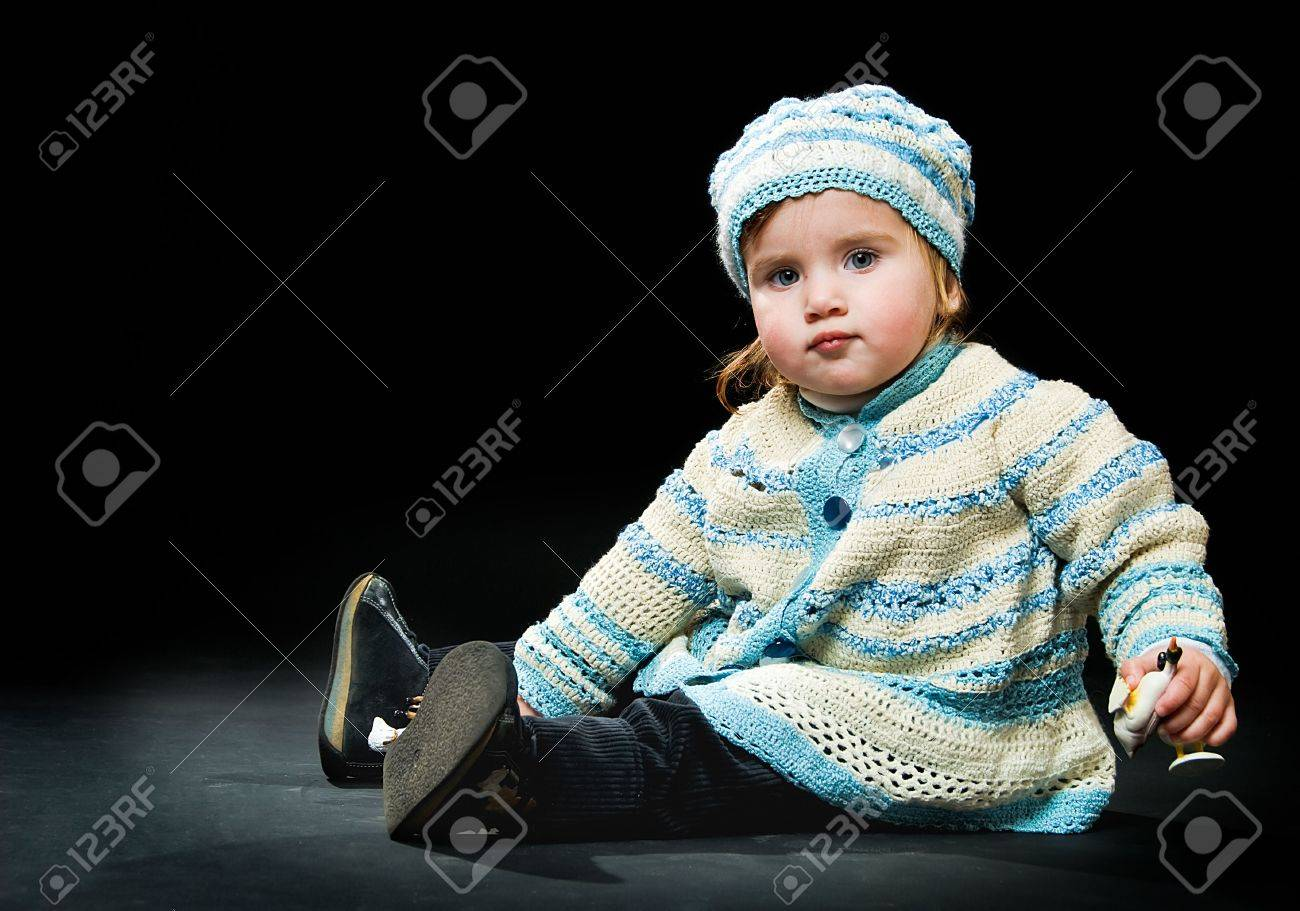 sitting little baby in a bound suit on black background Stock Photo - 5287947