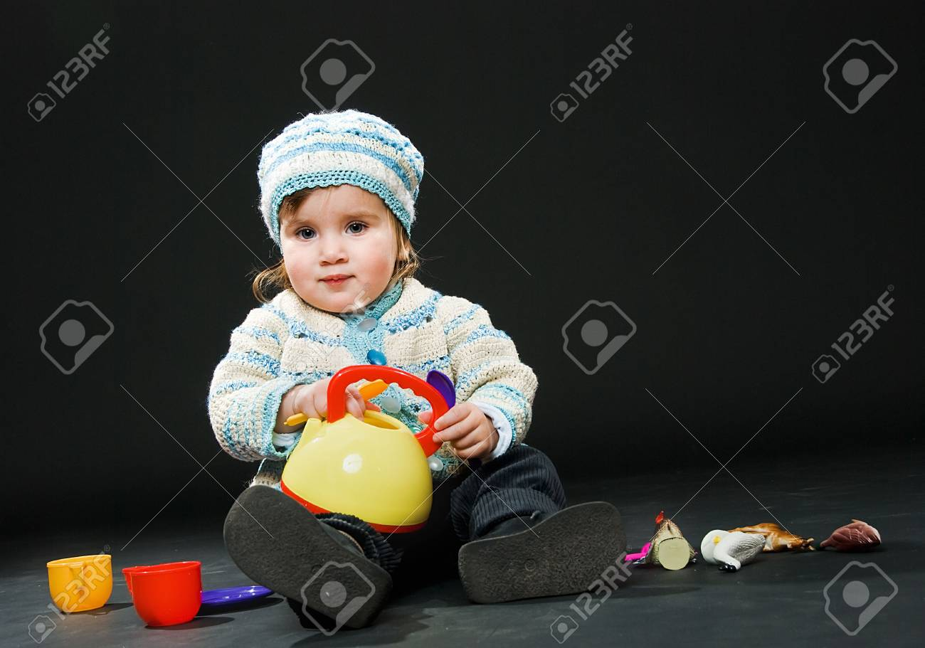 sitting little baby in a bound suit with toys on black background Stock Photo - 5341070