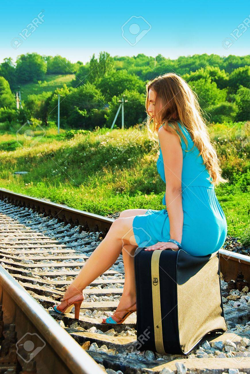 pretty girl sitting on a suitcase on the train tracks Stock Photo - 5405042