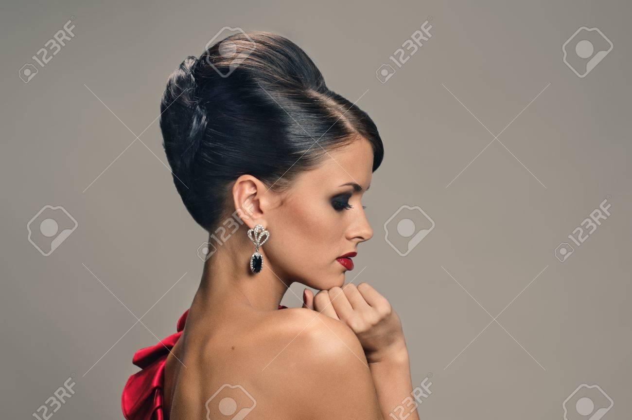 Banque dimages , portrait de belle fille avec coiffure élégante et robe rouge sur fond gris