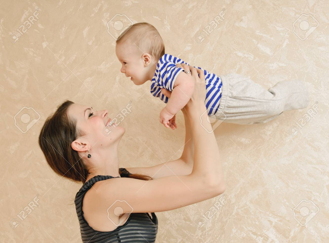young mother and her baby in the room about wall with wall-paper Stock Photo - 13586190