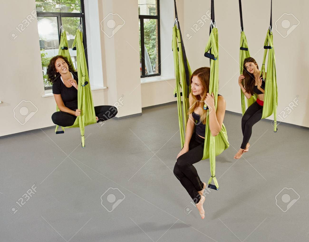 young women posing in anti gravity aerial yoga green hammock  indoor fitness club  young women posing in anti gravity aerial yoga green hammock      rh   123rf