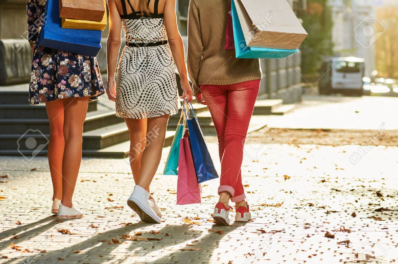 Girls Women Friends With Sexy Legs Walking From Back With Shopping Bags Stock Photo