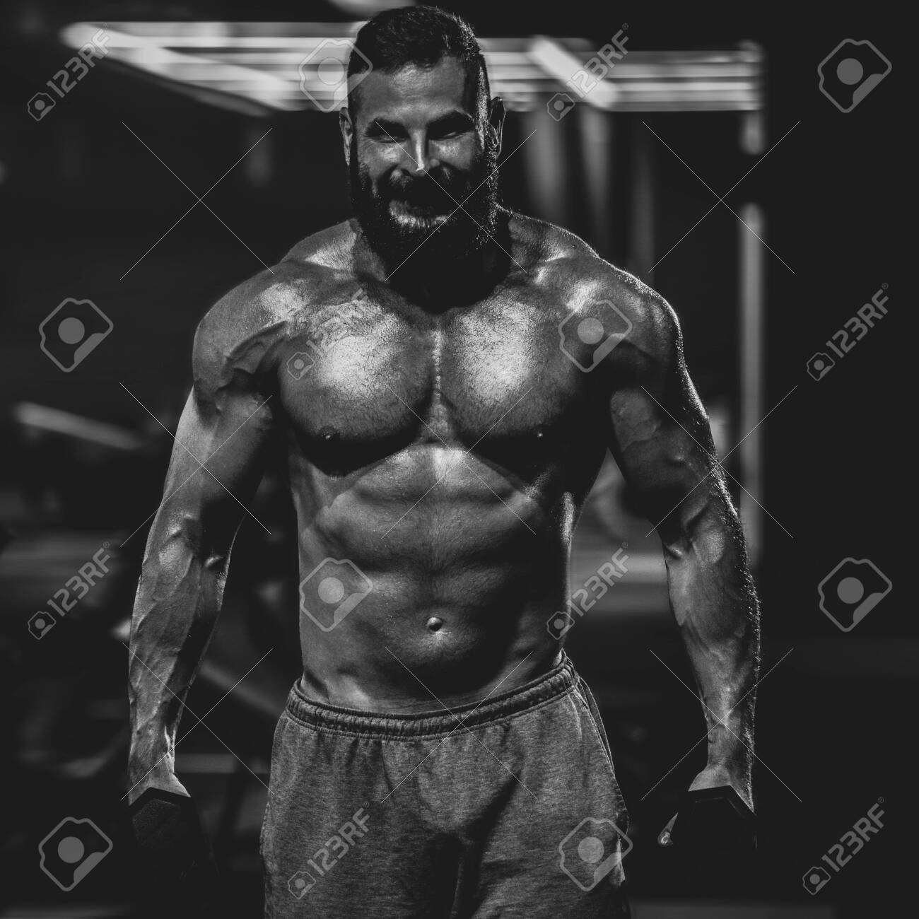 Young powerful fit man doing biceps lifting with dumbbells, dramatic black and white image - 139936563