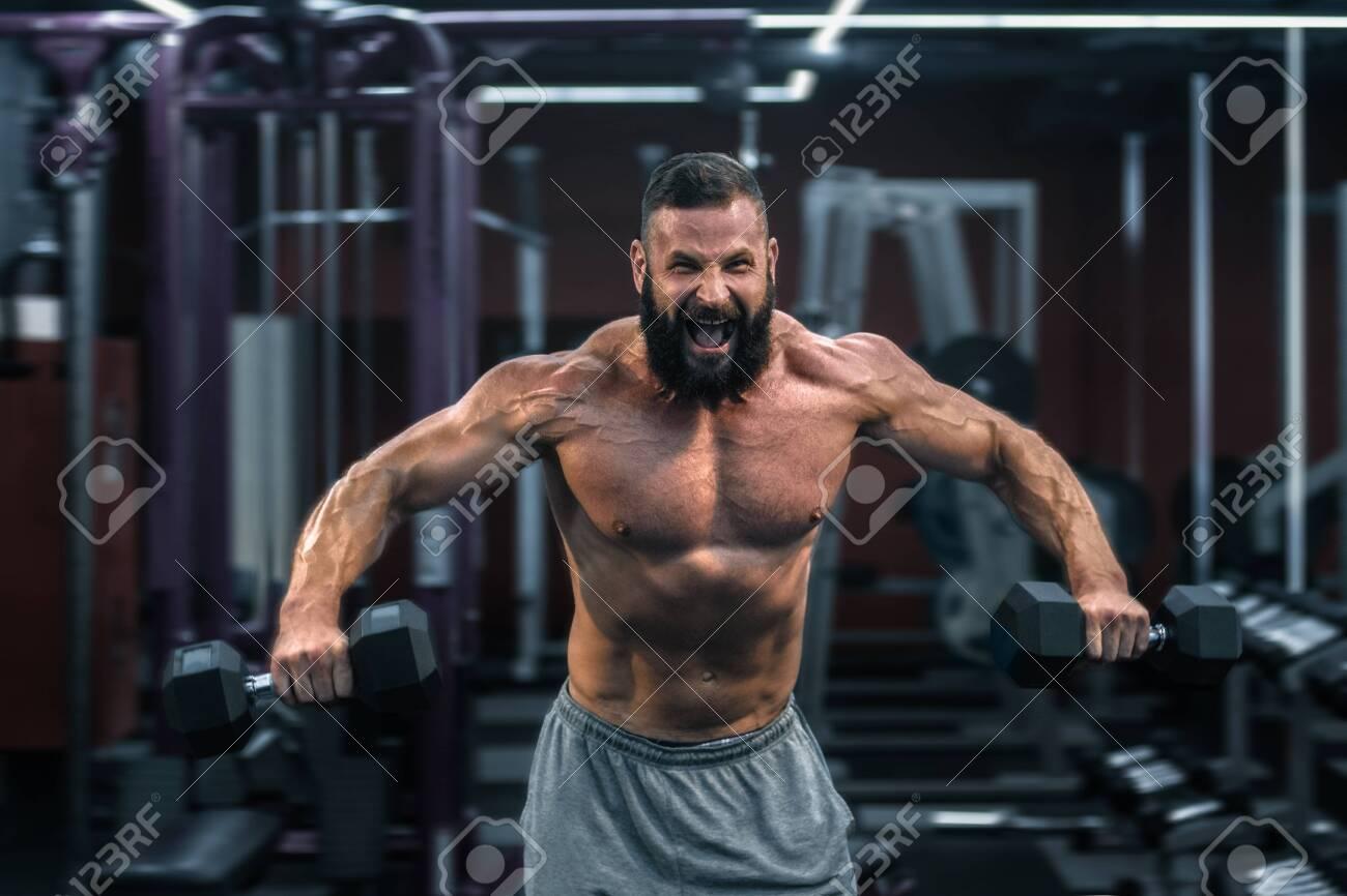 Muscular athletic bodybuilder working hard in gym on dark background - 143479477