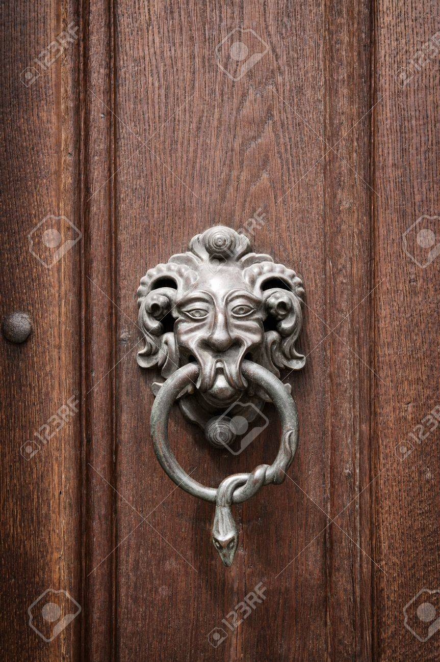 Gargoyle head door knocker with a snake encoiled ring in its mouth welcomes visitors on an & Gargoyle Head Door Knocker With A Snake Encoiled Ring In Its.. Stock ...