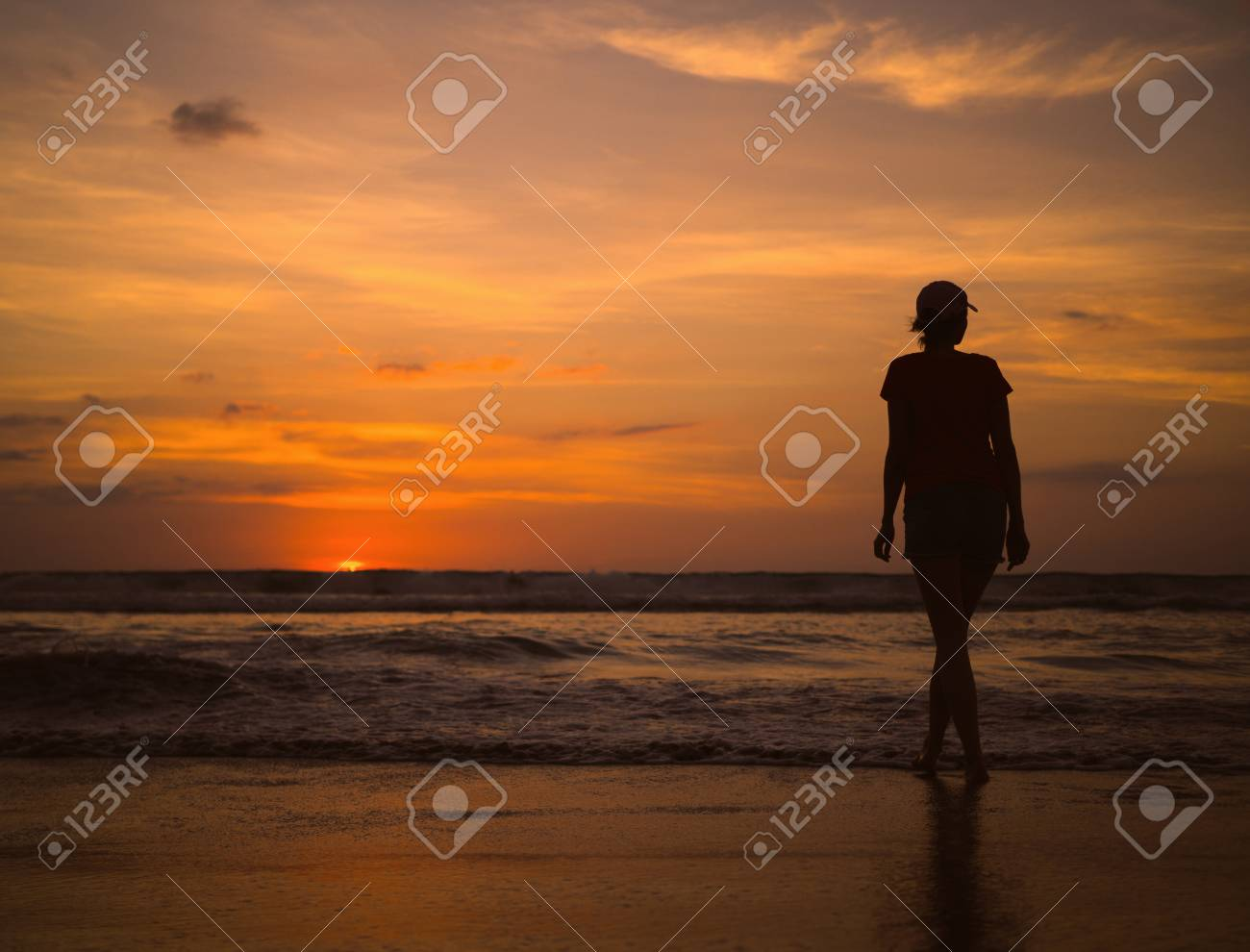 Young Beautiful Slim Girl On The Beach Watching Sunset And