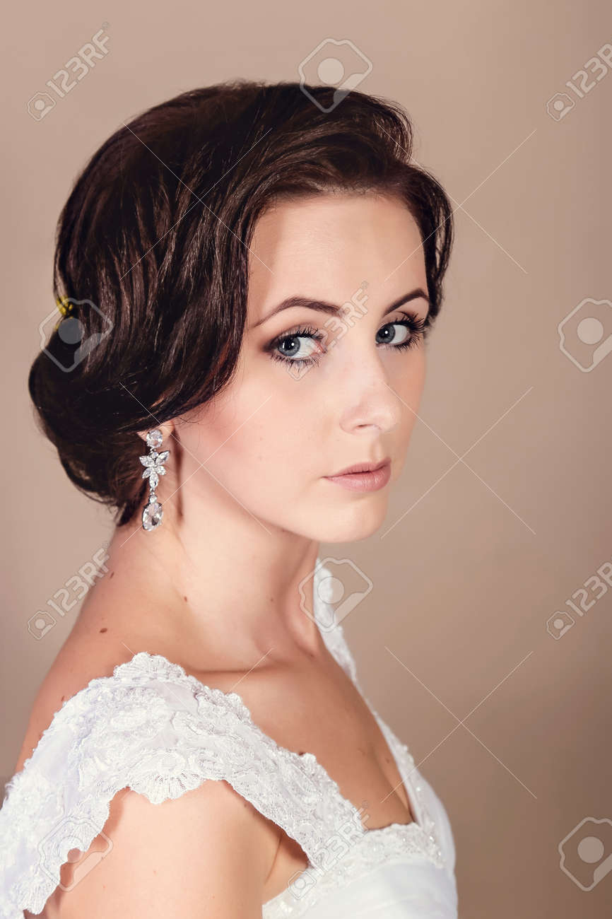 Beautiful bride posing in her wedding day in studio on a beige background. Happy girl holding a basket with a bouquet of tulips - 146686850