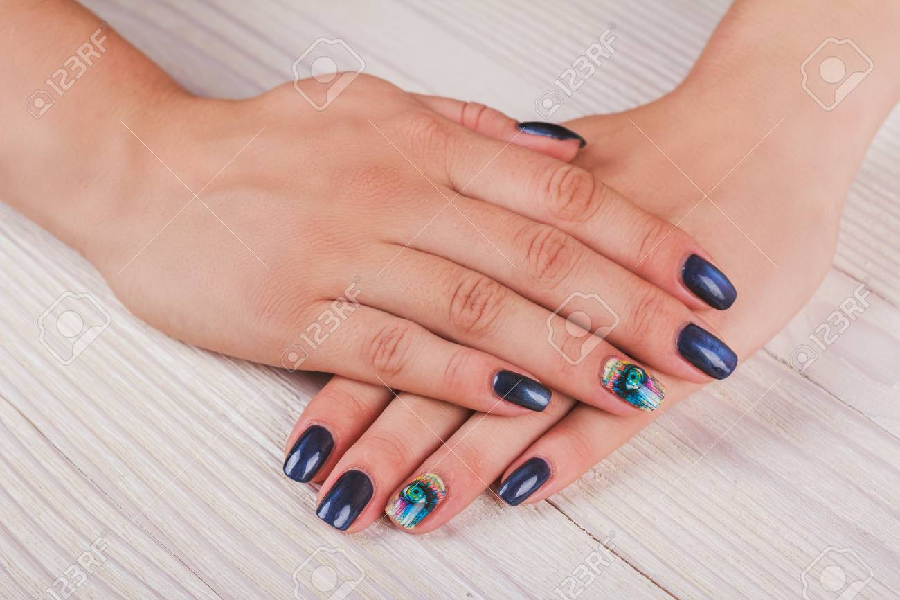 Dark Blue Nail Art With Print Eye On Light Wood Background Stock