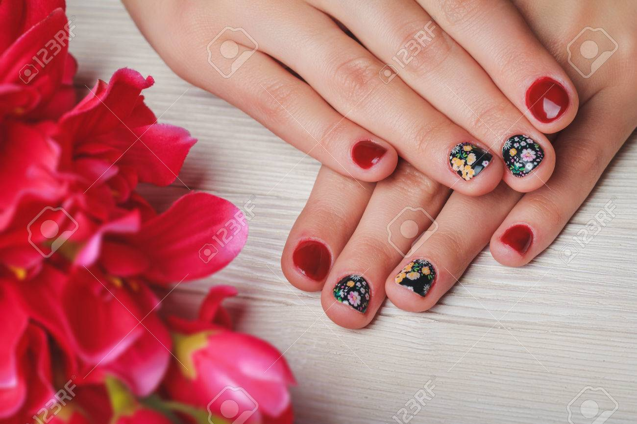 Red Nail Art With Printed Flowers On Light Wooden Background Stock