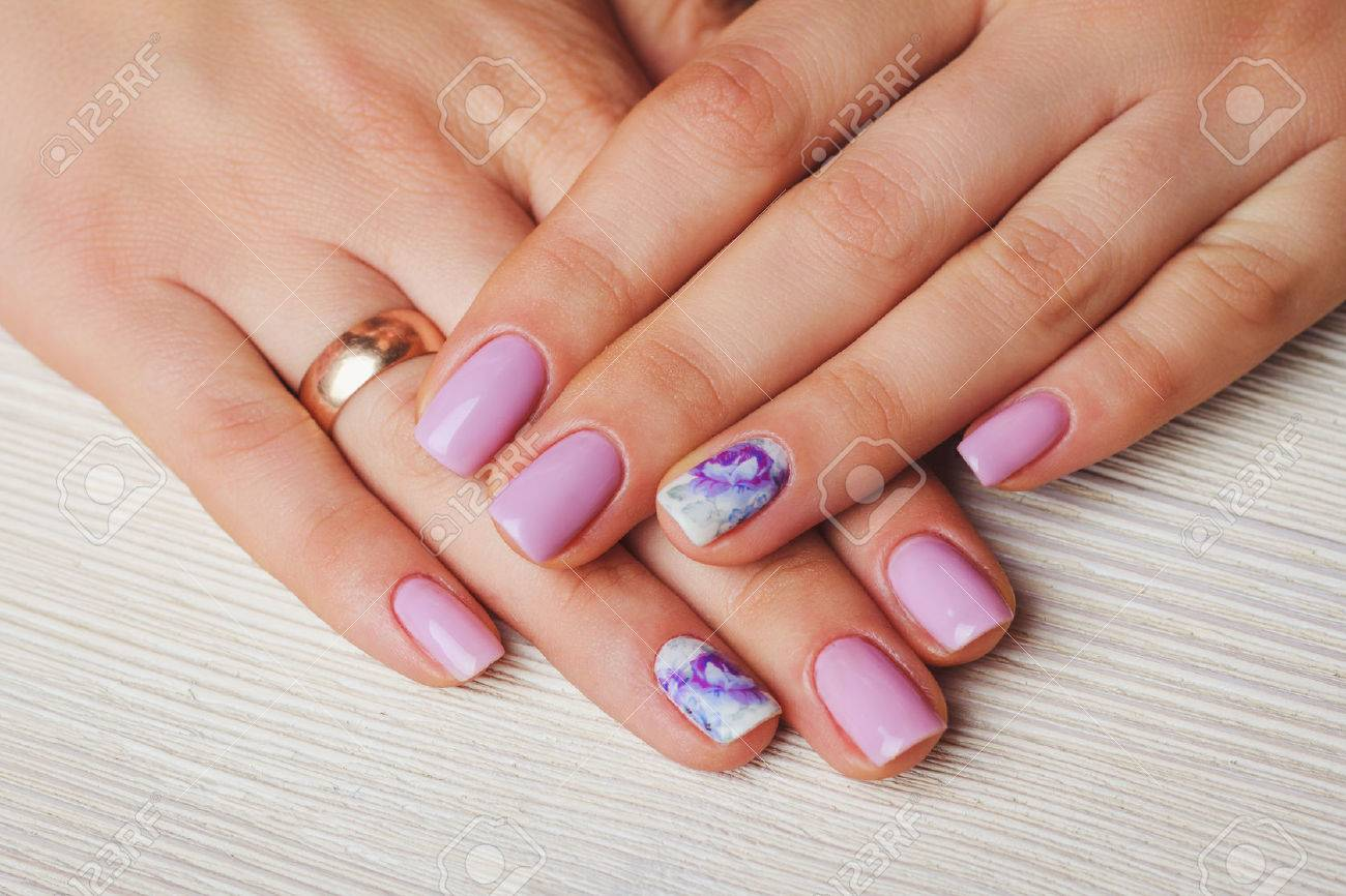 Lilac Nail Art With Printed Flowers On Light Wooden Background Stock