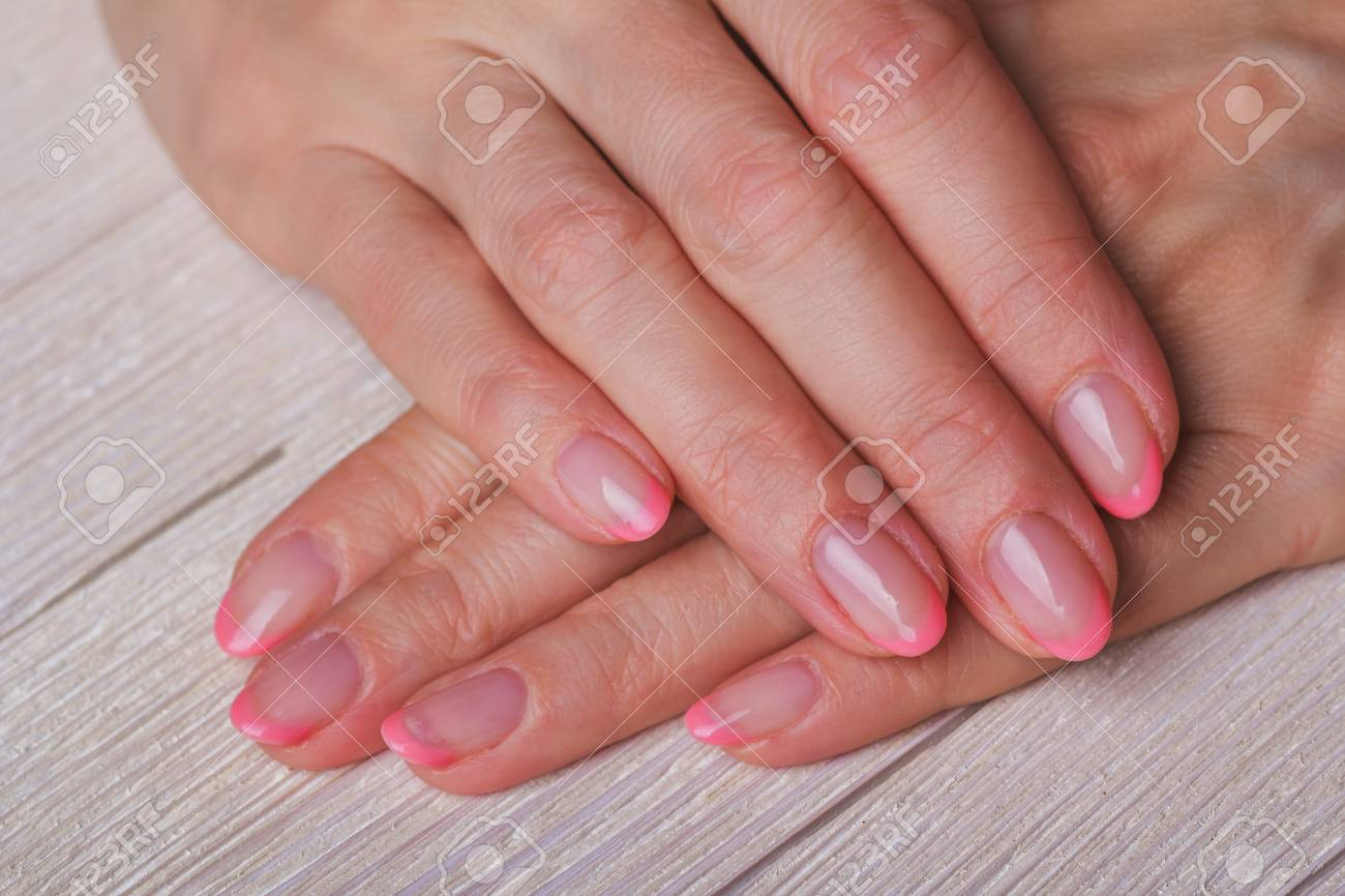 French Nail Art In Light Pink Colour On Light Wooden Background