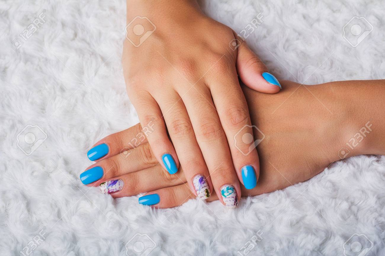 Light Blue Nail Art With Feathers Print On Light Background Stock