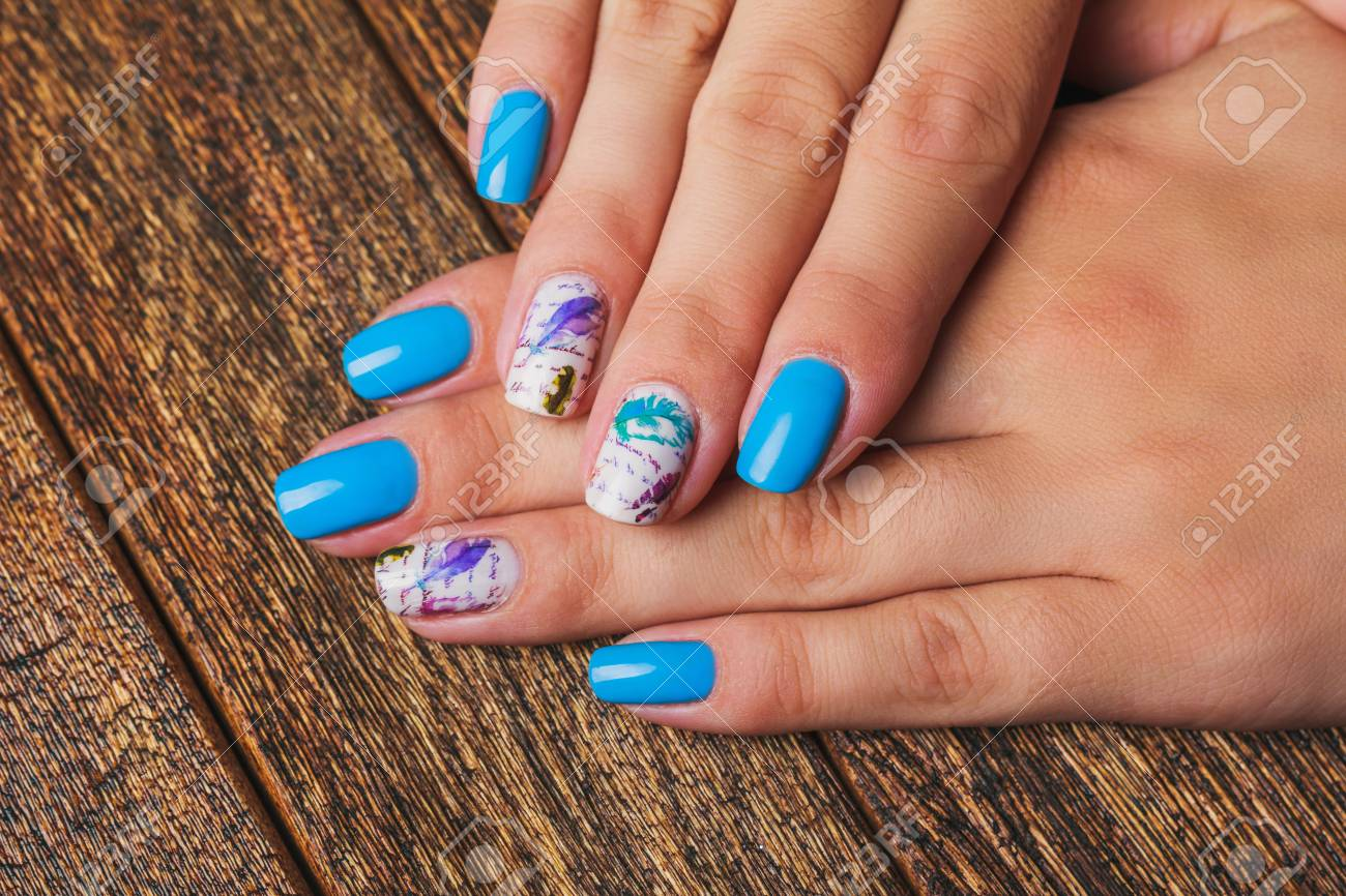 Light Blue Nail Art With Feathers Print On Wooden Background Stock ...
