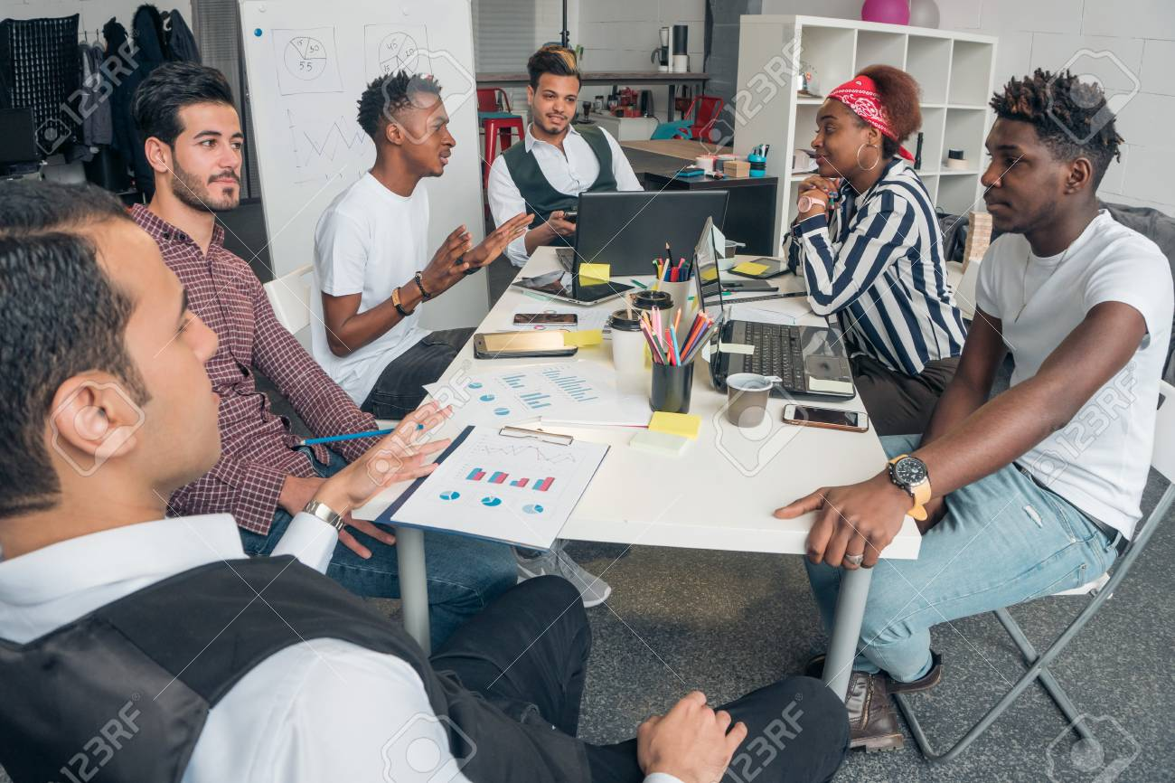 Young promising guys discuss innovative projects in the office. - 121542194