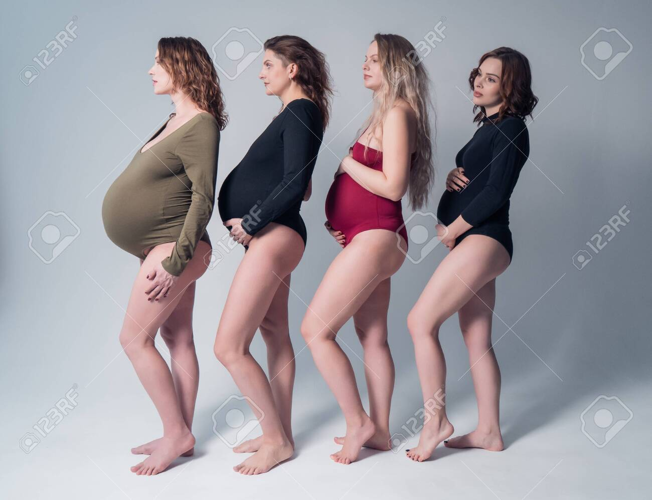 Four beautiful pregnant woman in swimsuit standing one behind the other on a white background. - 140600163