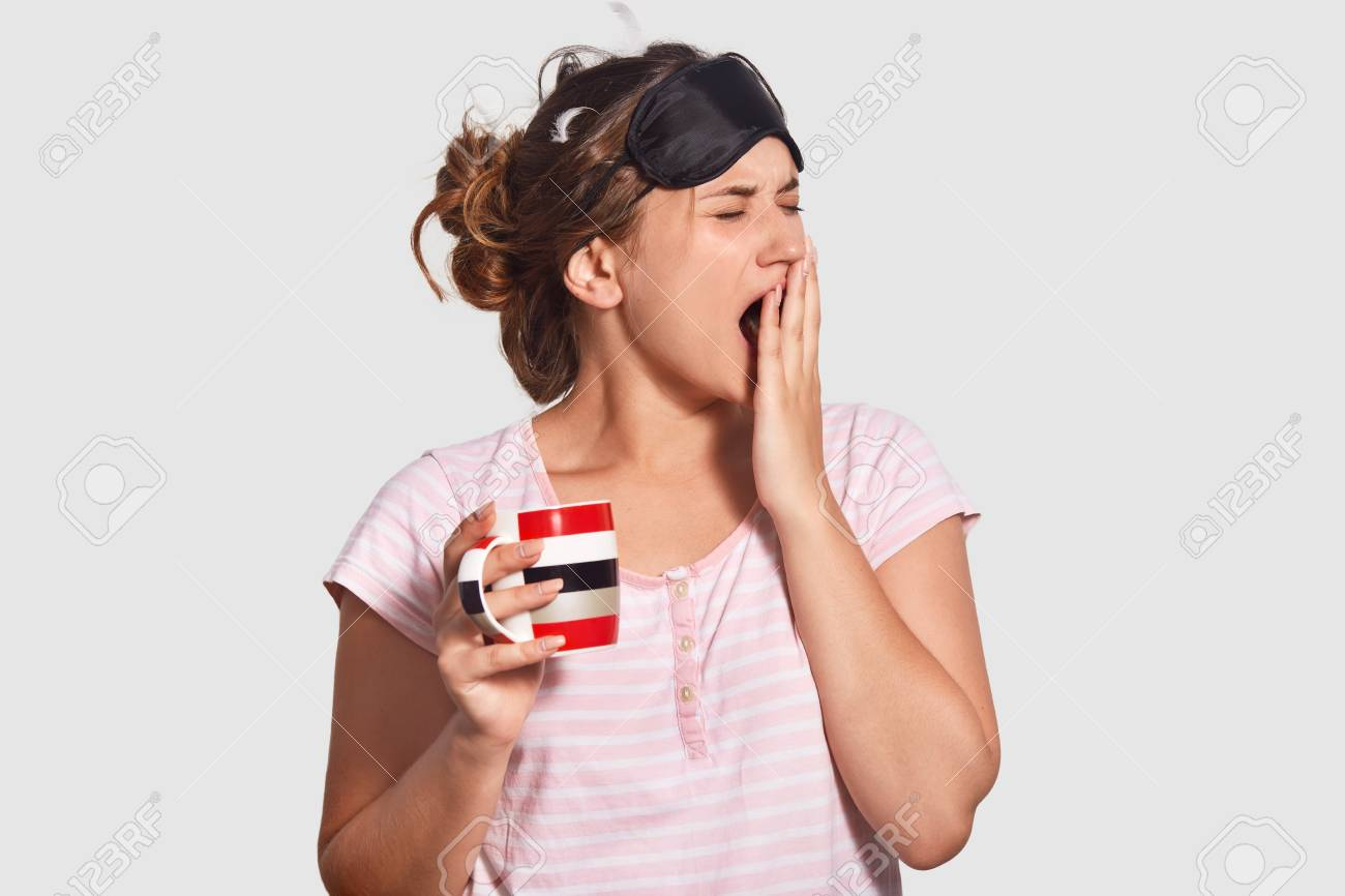 Indoor shot of beautiful female wants sleep badly, yawns and closes mouth with hand, wears blindfold and casual t shirt, holds mug with refreshing beverage, stands against white background - 108834217