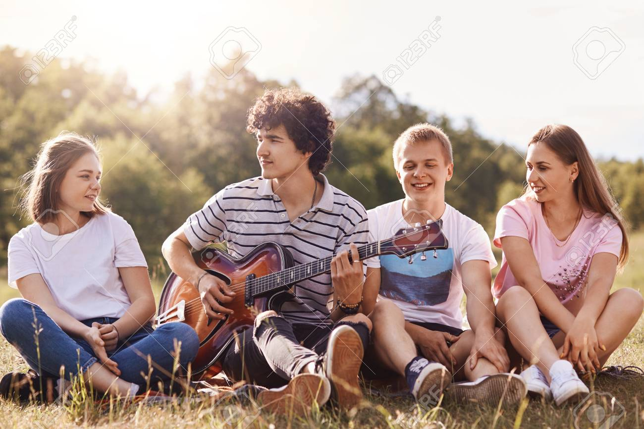 Friends enjoying singing songs, spending time together, have good mood, celebratng someone's birthday, spend sunny summer day with friends, have happy facial expression. Friendship and people concept - 121070541
