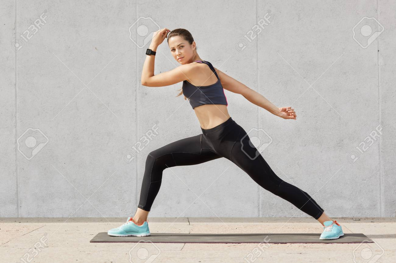 Fit and healthy woman stretches before running, Caucasian female wearing tank top, black legging and blue sneakers doing sport exercises on mat in gym, model posing alone over grey background. - 123902057