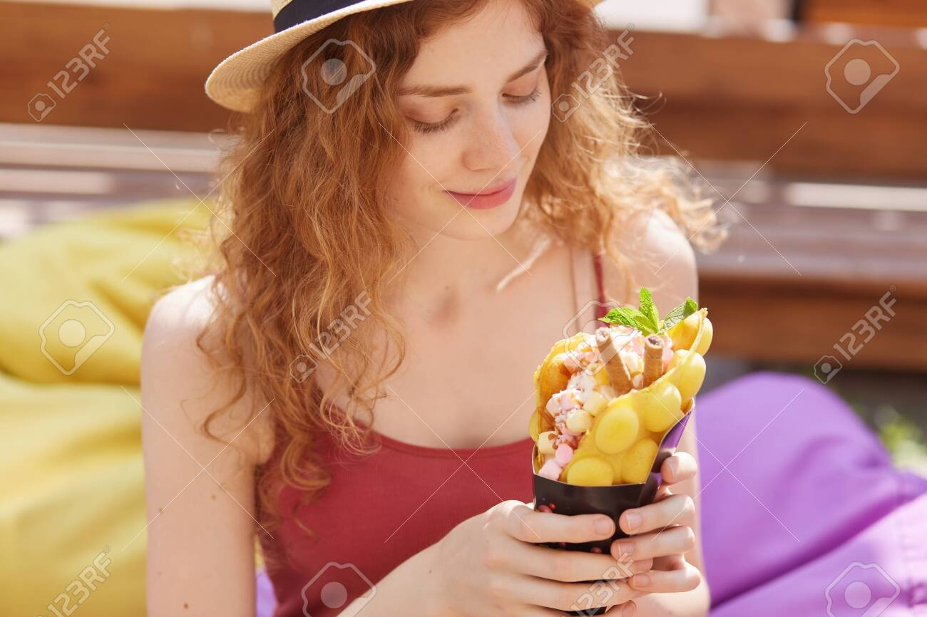 Portrait of young adorable female looking at her dessert with delight, being in good mood, chilling out alone, enjoying warm sunny day, wearing casual items of clothes. People and food concept. - 129221702